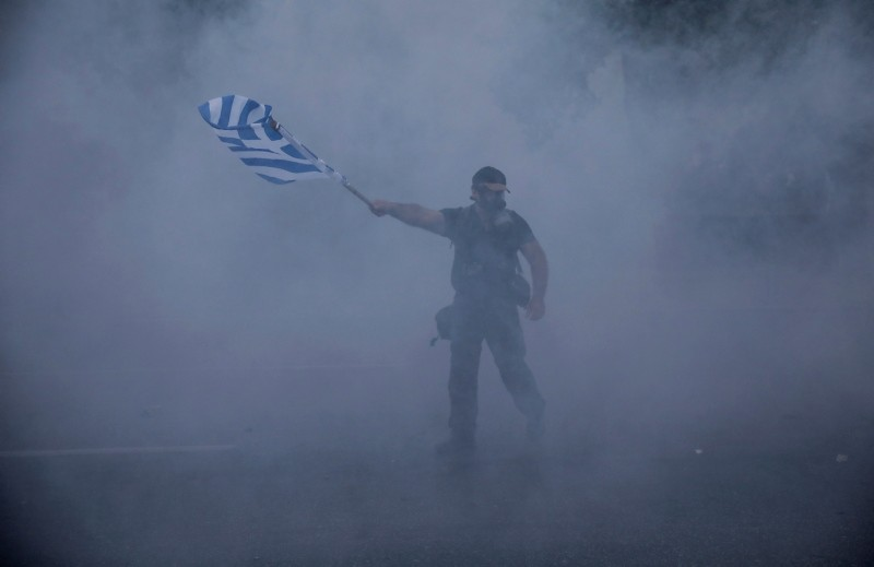 A protester waves a Greek flag amid tear gas smoke during clashes at the northern Greek city of Thessaloniki, Saturday, Sept. 8, 2018. (AP Photo)