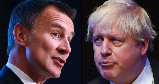 Britain's Foreign Secretary Jeremy Hunt (L) has called on his rival Boris Johnson (R) to man up over a domestic row scandal. (AFP Photo)