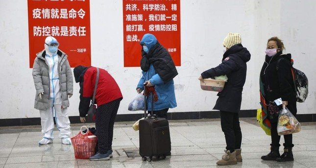 A medical worker in a protective suit looks at patients who diagnosed with the coronaviruses arrive at a temporary hospital which transformed from an exhibition center in Wuhan in central China's Hubei province, Feb. 5, 2020. AP Photo