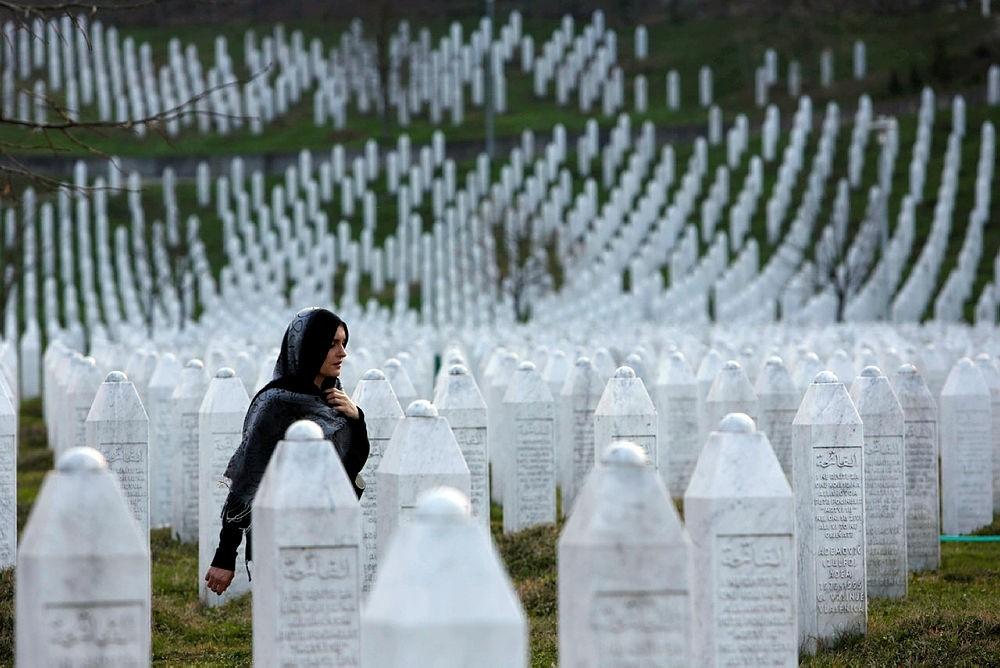 A Bosnian woman walks among gravestones at Memorial Centre Potocari near Srebrenica, Bosnia and Herzegovina. (AP Photo)