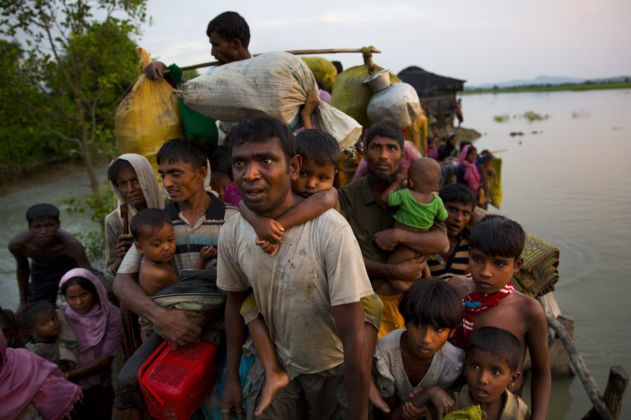 n this Nov. 1, 2017, file photo, Rohingya Muslims carry their young children and belongings after crossing the border from Myanmar into Bangladesh, near Palong Khali, Bangladesh (AP Photo)