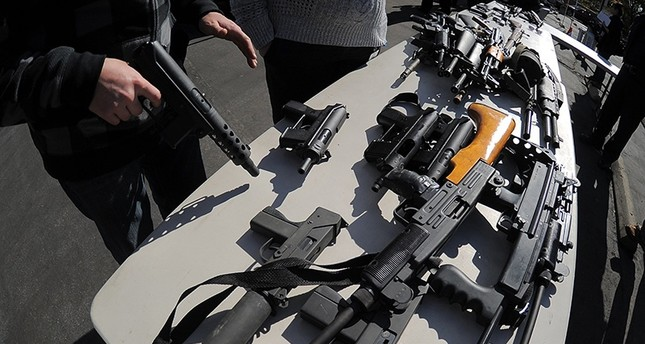 An LAPD officer stands before collected assault weapons during the LAPD Gun Buyback Program event  in the Van Nuys area of north Los Angeles,  on December 26, 2012. (AFP Photo)
