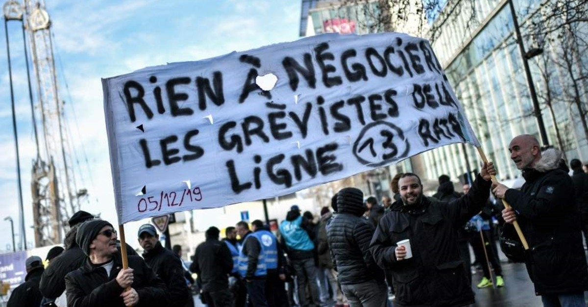 Paris metro operator RATP employees hold a protest banner, Dec. 24, 2019. (AFP Photo)
