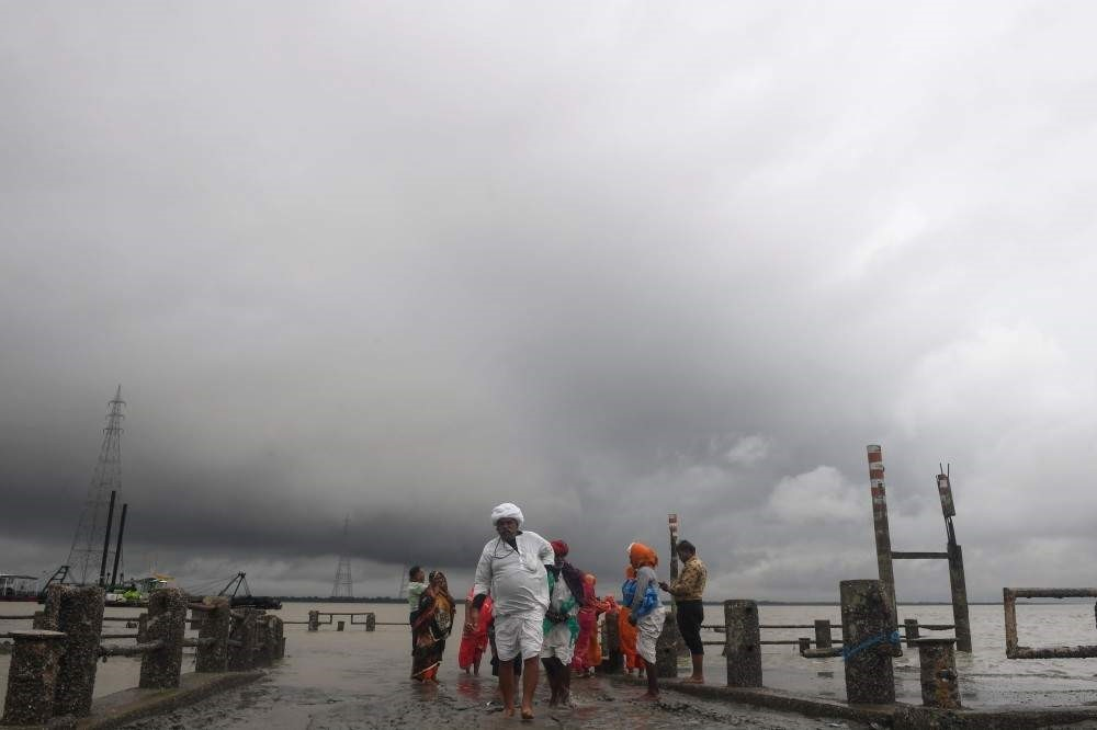 Hindu pilgrims walk back from the dock after a ferry service to Sagar Island was suspended due to the approaching Cyclone Bulbul in Kakdwip in West Bengal state on Nov. 9, 2019 (AFP Photo)