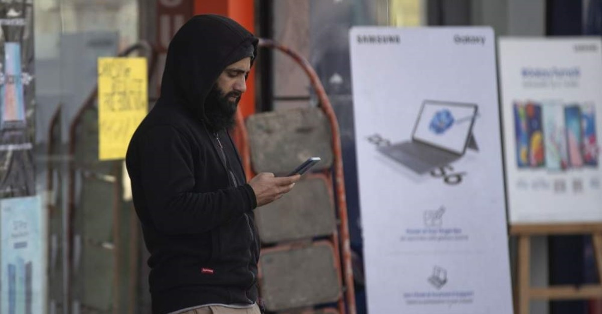 A Kashmiri man browses the internet on his mobile phone outside a shop, Srinagar, Jan. 30, 2020. (AP Photo)