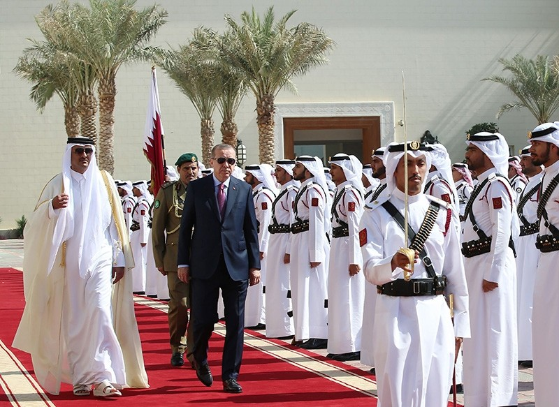 President Recep Tayyip Erdogan (C-L) being welcomed by Qatar's Emir Sheikh Tamim bin Hamad Al-Thani (L) as they review an honour guard upon his reception in the capital Doha. (AFP Photo)
