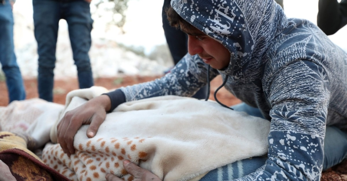 A young Syrian man mourns over the blanket-clad body of a child, killed along with six other members of a family, in a house hit in a reported airstrike by pro-regime forces in the town of Sarmin in the northern Syrian Idlib province on Feb. 2 (AFP)