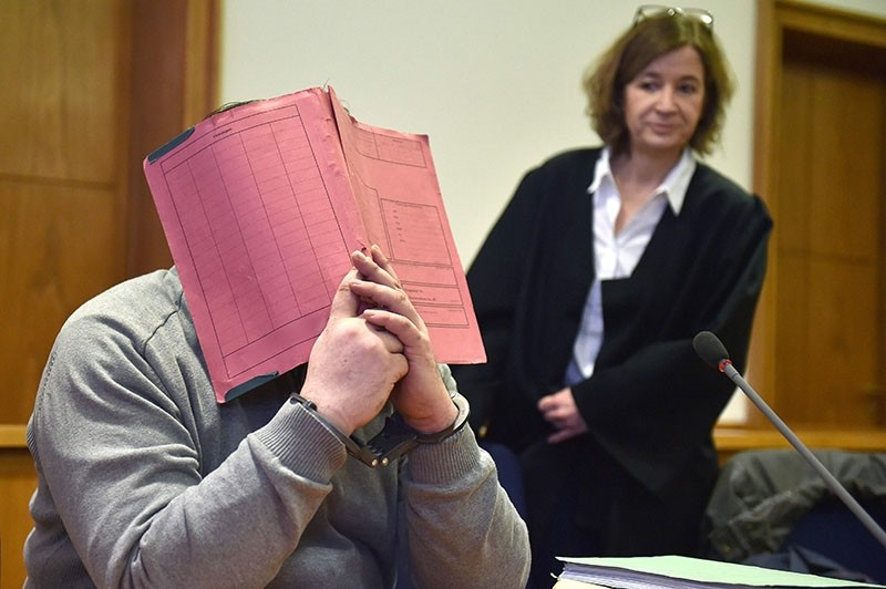 This file photo shows German former nurse Niels Hoegel hiding his face behind a folder as he waits next to his lawyer Ulrike Baumann (R) for the opening of another session of his trial at court in Oldenburg, NW Germany, on Feb. 26, 2015. (AFP PHOTO)
