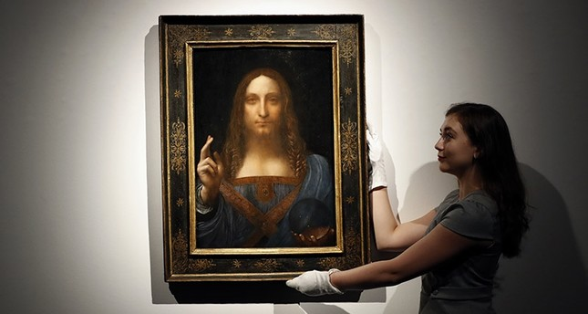 In this Oct. 24, 2017 file photo, an employee poses with Leonardo da Vinci's Salvator Mundi on display at Christie's auction rooms in London. (AP Photo)