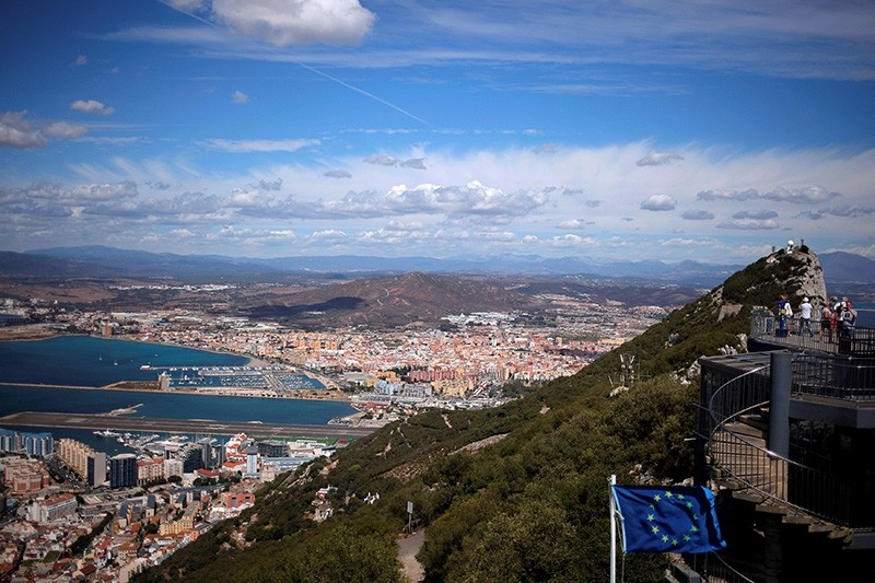 The Spanish city of La Linea de la Concepcion (rear) and tarmac of the Gibraltar International Airport (bottom L) sa tourists stand on the top of the Rock next to the EU flag, in the British territory of Gibraltar, Sept. 14, 2016. (Reuters Photo)