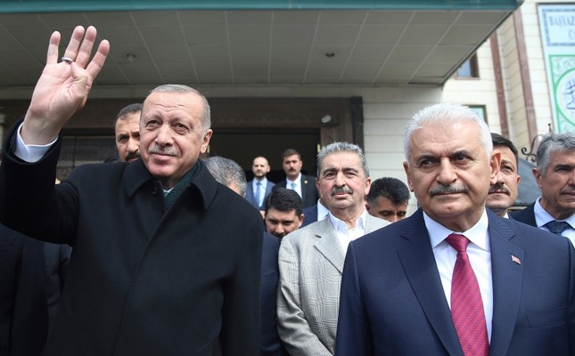 President Recep Tayyip Erdoğan, left, is flanked by the ruling Justice and Development Party (AK Party)'s mayoral candidate for Istanbul, Binali Yıldırım, waves after Friday prayers, in Ankara, Turkey, Friday, April 12, 2019. (AP Photo)