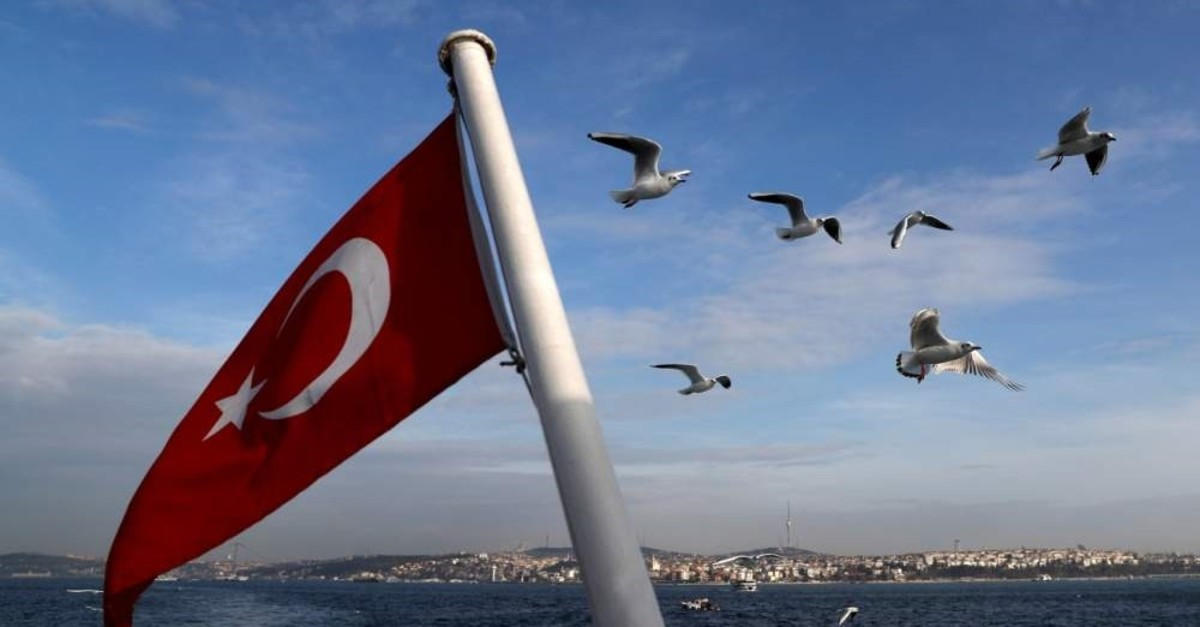 A Turkish flag flies on a passenger ferry with the Bosphorus in the background in Istanbul, Jan. 27, 2020. (REUTERS)