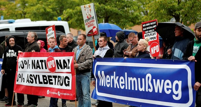 Protesters hold sign that reads Merkel must go prior to the election campaign rally of German Chancellor Angela Merkel in Wolgast, Germany, September 8, 2017. (REUTERS Photo)