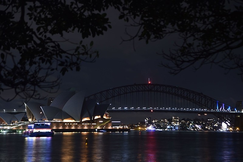 Sydney Harbour Bridge and the Opera House are plunged into darkness for the Earth Hour environmental campaign on March 24, 2018 (AFP Photo)