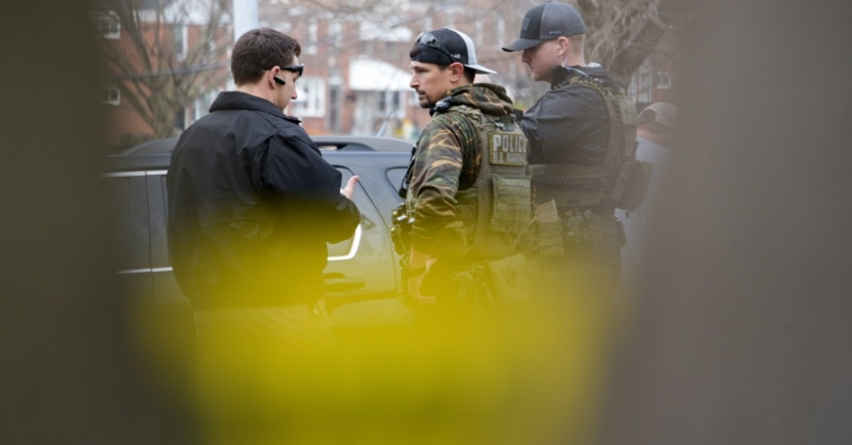 Law enforcement personnel work at the scene of a shooting, Wednesday, Feb. 12, 2020, in Baltimore. (The Baltimore Sun via AP)