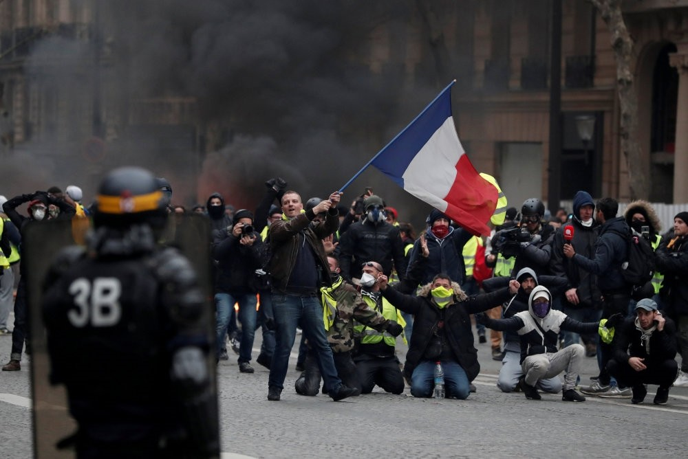 A protester waves a French flag during clashes with police at a demonstration by the ,yellow vests, movement in Paris, Dec. 8.