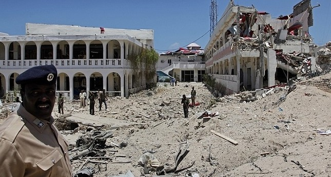 Somali soldiers stand near to a building destroyed by a blast near the presidential palace in the capital Mogadishu, Somalia, Aug. 30, 2016. AP Photo