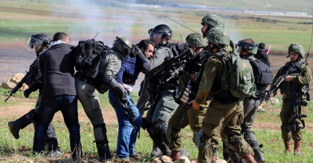 Israeli soldiers arrest a Palestinian protester during a demonstration outside the West Bank village of Tamun near the Jordan Valley, Jan. 31, 2020. (AFP Photo)