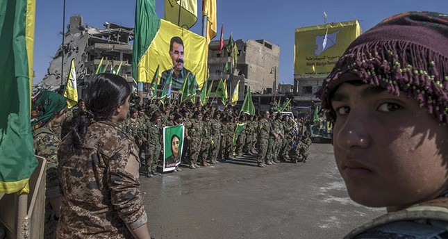 In this Thursday, Oct. 19, 2017 photo, militants from the PKK-affiliated Women's Protection Units (YPJ) hold a celebration in Paradise Square in Raqqa, Syria. The giant poster behined them features PKK's jailed leader Abdullah Öcalan. (AP Photo)