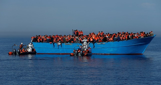 Migrants on a wooden boat are rescued by the Malta-based NGO Migrant Offshore Aid Station (MOAS) in the central Mediterranean in international waters off the coast of Sabratha in Libya, April 15, 2017. (Reuters Photo)