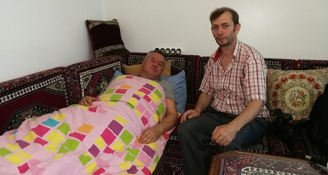 Mehmet Kara (L) recuperates in his home. (DHA Photo)