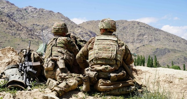 In this file photo taken on June 6, 2019, US soldiers look out over hillsides during a visit of the commander of US and NATO forces in Afghanistan General Scott Miller at the Afghan National Army ANA checkpoint in Nerkh district of Wardak province.