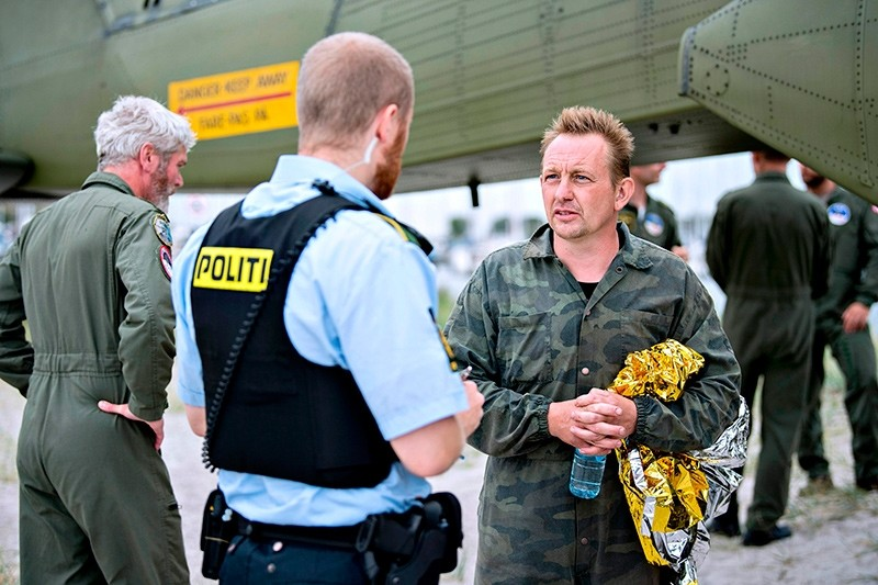 Peter Madsen (R), builder and captain of the private submarine ,UC3 Nautilus, talks to a police officer in Dragoer Harbor south of Copenhagen on Friday, August 11, 2017 (AFP Photo)