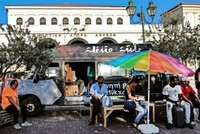 The brightly colored minivan that pulls into Athens' food market, drawing a group of refugees around it, is not carrying something edible.  The contents - hundreds of books - are there to satisfy...
