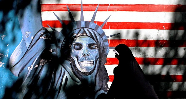 Iranian woman walks past graffiti art characterizing the U.S. Statue of Liberty, painted on the wall of the former U.S. Embassy in Tehran, Iran. (AP Photo)