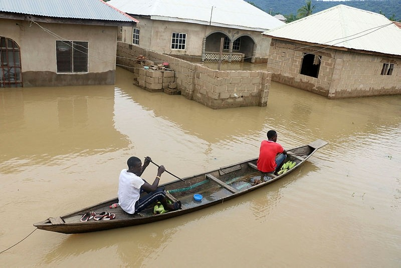 Residents steer a dugout canoe past flooded houses following heavy rain in the Nigerian town of Lokoja, in Kogi State, on September 14, 2018.  (AFP Photo)