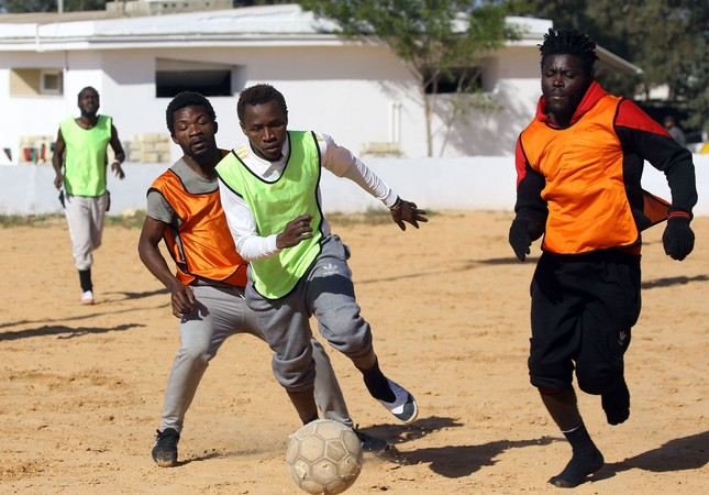 Cameroonian (orange) and Senegalese (yellow) African migrants, split into two teams for a football match at the Libyan Interior Ministry's illegal migration shelter in Tajoura.