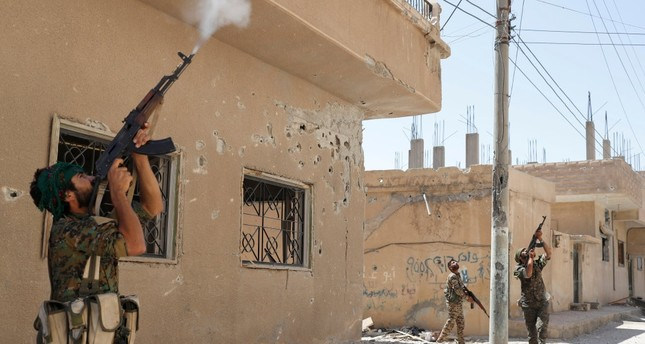 The YPG terrorists fire rifles at a drone in Raqqa, Syria, June 16.
