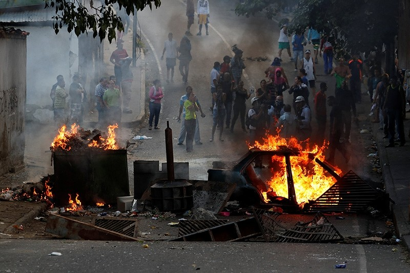 Demonstrators stand behind a burning barricade during a protest close to a National Guard outpost in Caracas, Venezuela, Jan. 21, 2019. (Reuters Photo)