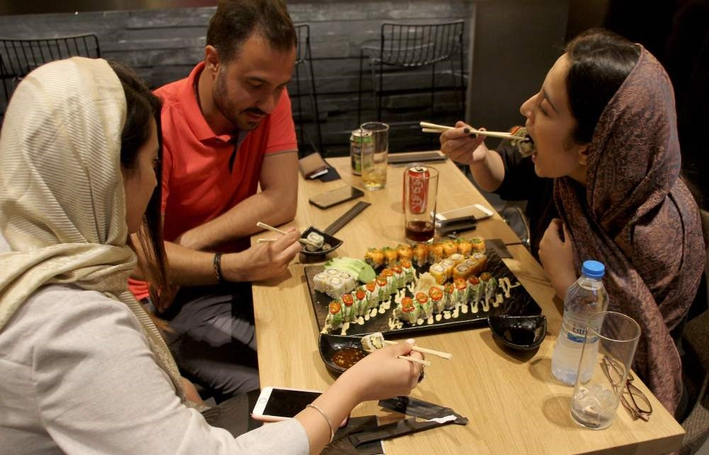 Iranians eat at a high-end French sushi chain that opened the previous week in northern Tehran.