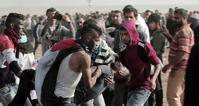 Palestinian protesters evacuate a young protester wounded by Israeli troops along Gaza's border with Israel, Friday, April 13, 2018. AP Photo