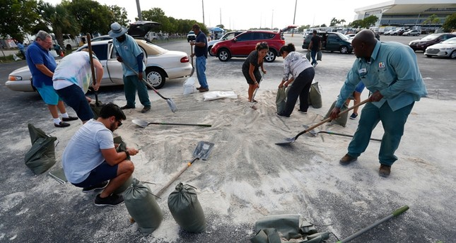 Residents fill up sandbags with the last bits of sand available in preparation for Hurricane Dorian, Friday, Aug. 30, 2019, in Hallandale Beach, Fla. AP Photo