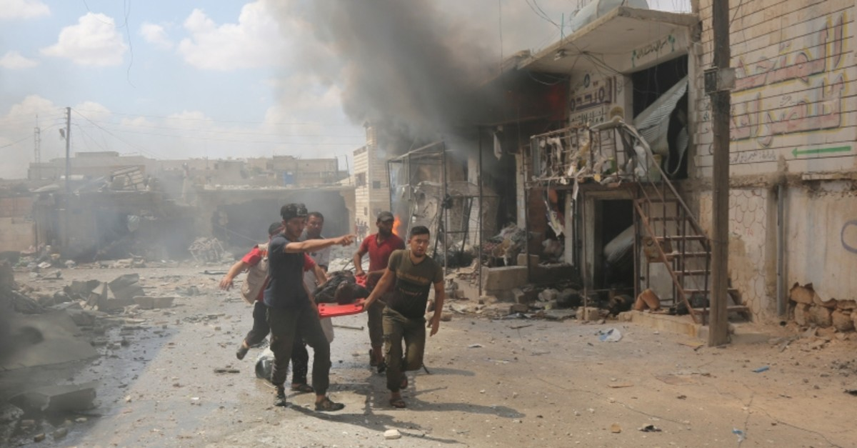 Syrians carry an injured civilian after an Assad regime bombing against Idlib in July 2019 (AA Photo)