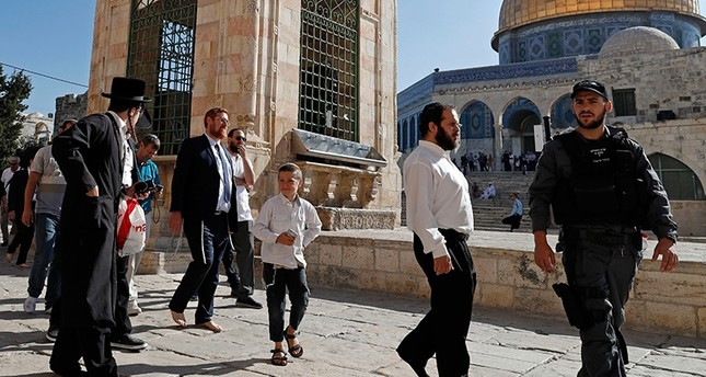 Far right Israeli Rabbi and Israeli lawmaker Yehuda Glick (C-L) walks barefoot, escorted by Israeli police and supporters, inside the flashpoint Al-Aqsa Mosque compound in Jerusalem, Aug. 29, 2017. (AFP Photo)