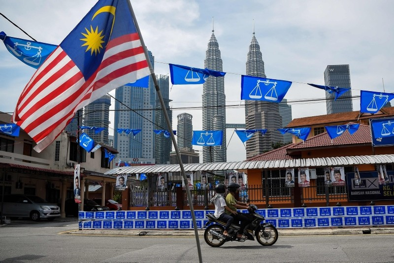 Malaysia's Petronas Twin Towers loom in the background as a motorist rides past the ruling coalition party Barisan Nasional's flags on the eve of the 14th general election in Kuala Lumpur on May 8, 2018. (AFP PHOTO)