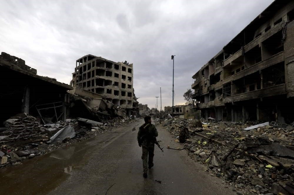 A SDF militant walks through a rubble-filled street surrounded by damaged buildings, Raqqa, Syria, Oct. 28.