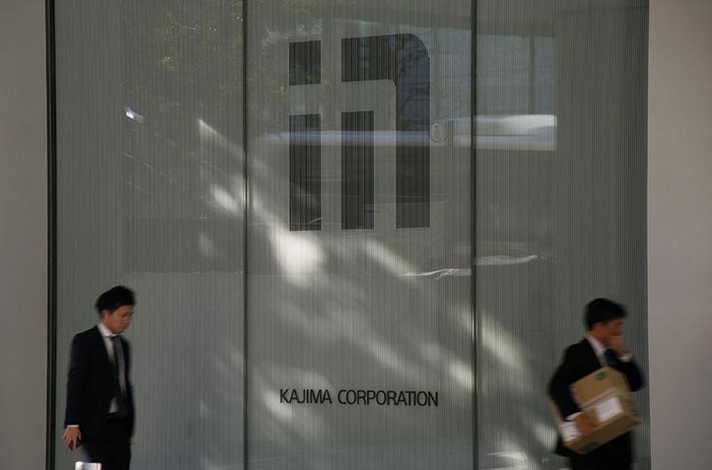 Men walk past the logo of Kajima Corp outside the company's headquarters in Tokyo, Japan, December 18, 2017. (Reuters Photo)