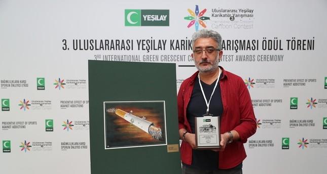 Grand prize winner Aşkın Ayrancıoğlu poses next to his work.