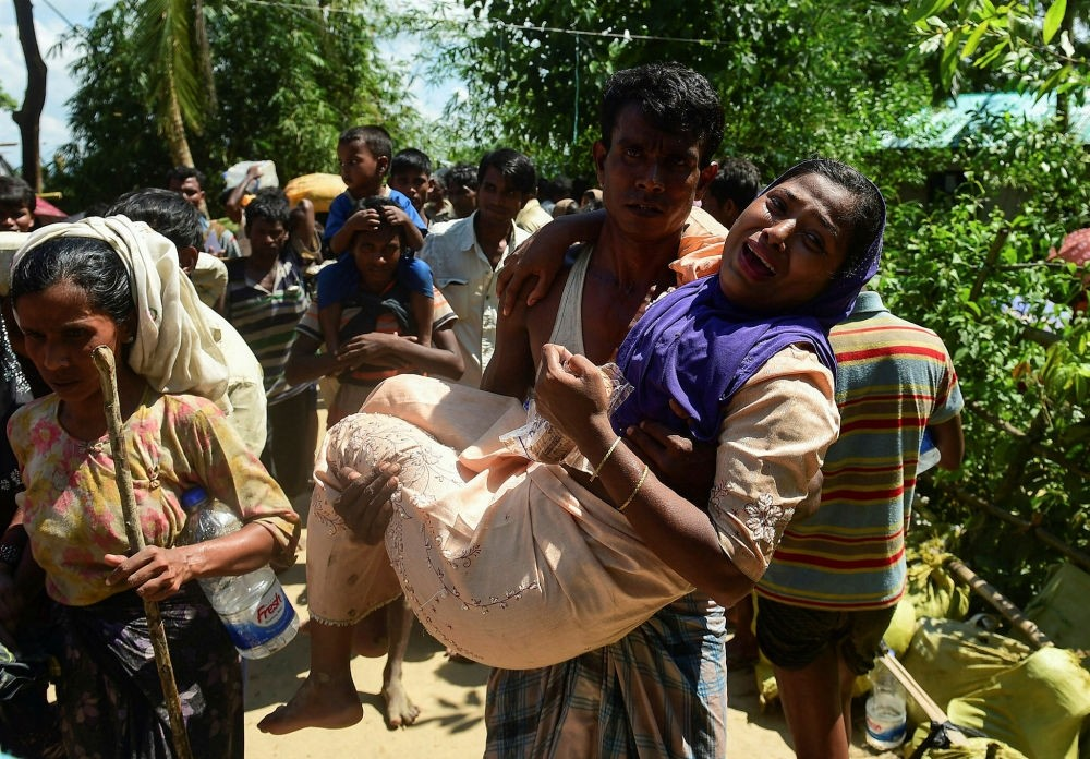 A Rohingya refugee carries his injured relative after crossing the Naf River as they flee violence in Myanmar to reach Bangladesh, Oct. 16.