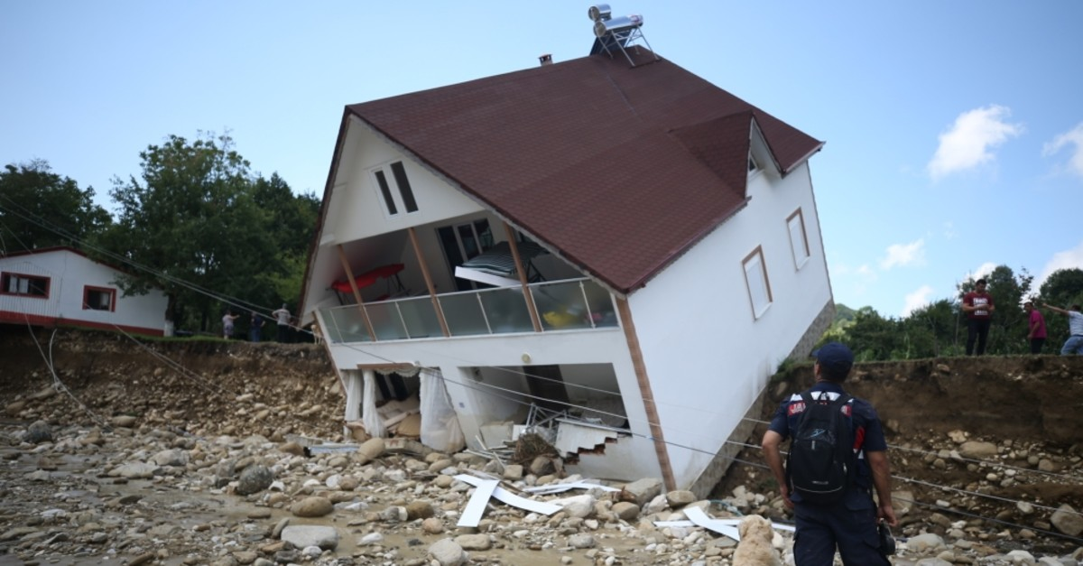 A gendarmerie personnel looks at a house tipped over due to floods in Esmahanu0131m village, Du00fczce, July 19, 2019.