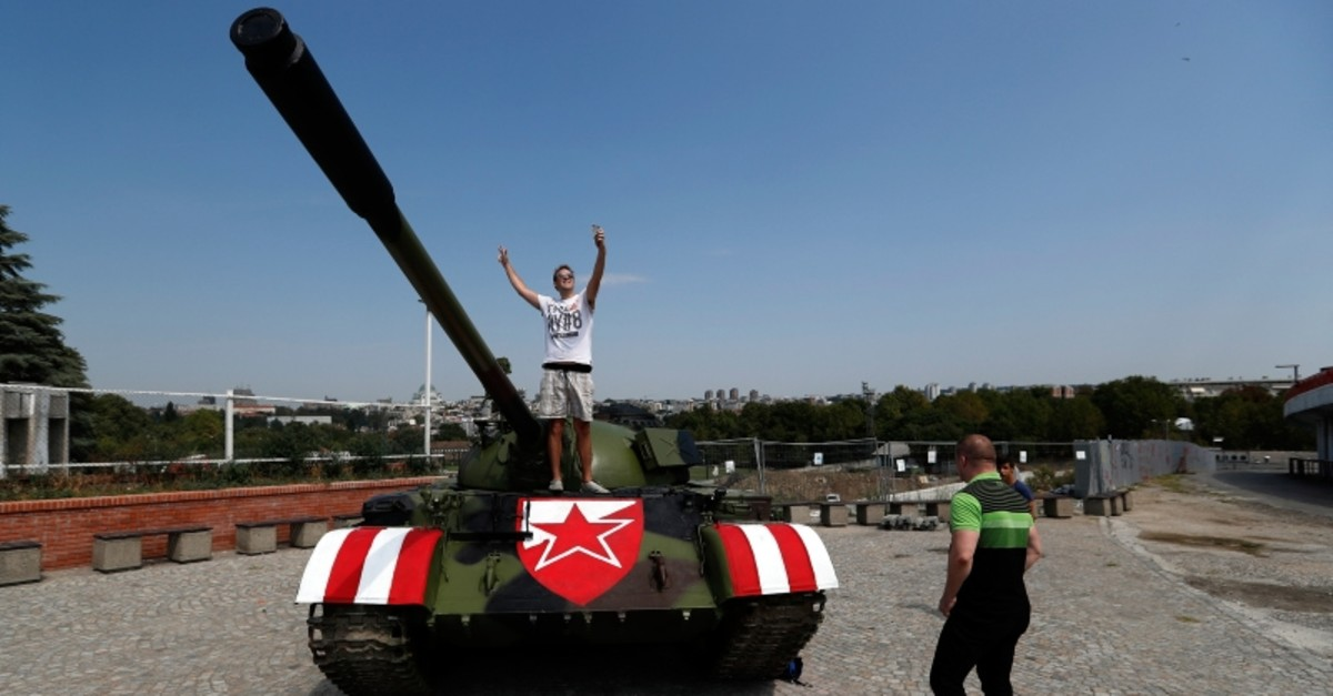 People pose with a former Yugoslav army T-55 battle tank seen in front of northern grandstand of Rajko Mitic stadium in Belgrade, Serbia, Tuesday, Aug. 27, 2019, placed as a gesture of support for the Red Star team. (AP Photo)