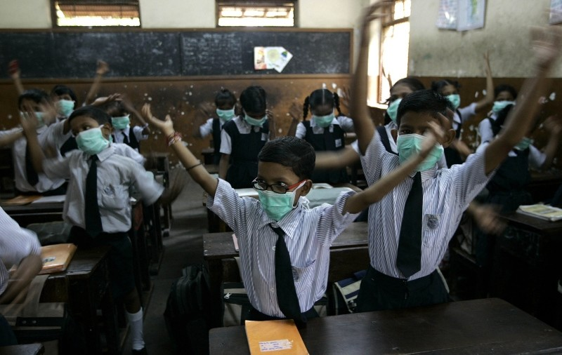 Children wearing masks to prevent spread of swine flu, sing in their classroom, in Mumbai, India, Monday, Aug. 10, 2009. (AP Photo)