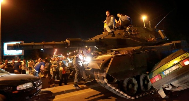People take over a tank as it crashes into a car during the coup attempt in Ankara on July 15, 2016.