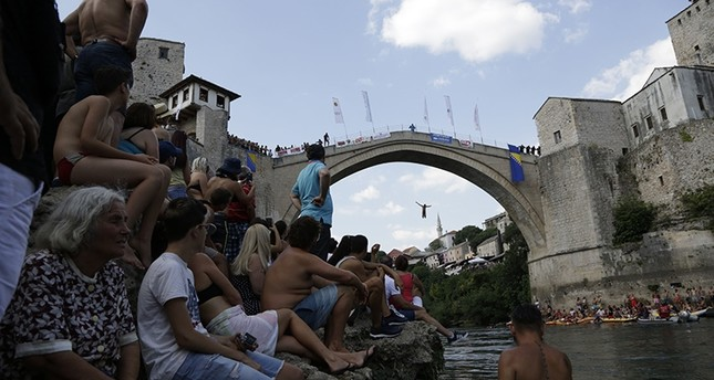 Spectators watch as a diver jumps from the Old Mostar Bridge during the 452nd traditional annual high diving competition, in Mostar, Bosnia, 140 kilometers (87 miles) south of the capital Sarajevo, Sunday, July 29, 2018. (AP Photo)
