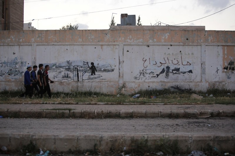 Rebel fighters and their families evacuated the besieged Waer district in central Syrian's Homs, after an agreement was reached between rebels and Syria's army. The text on the wall reads in Arabic:, Its time for goodbye., Reuters Photo