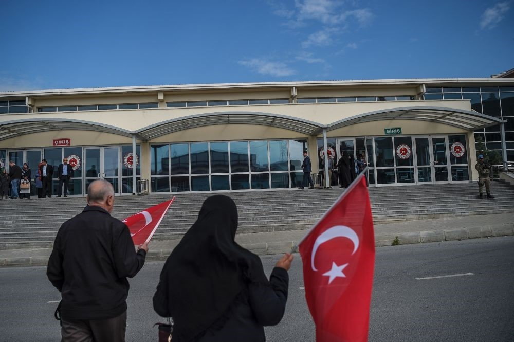 Relatives of coup victims hold Turkish flags as they wait outside the courthouse where putsch suspects are being tried in Istanbul.